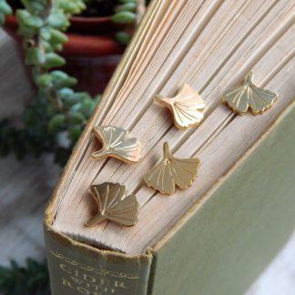 mini gold ginkgo pins balanced on a book